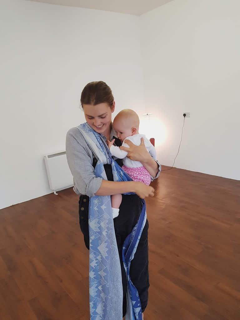 A Mum wrapping her baby in a woven wrap