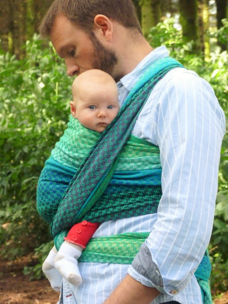 A dad carrying a baby outdoors